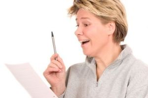 Blond mature woman looking at a document and looking as if she found the golden egg